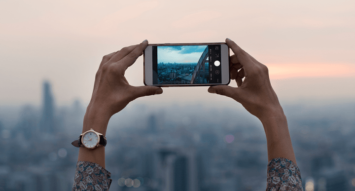 user taking smartphone photo of cityscape