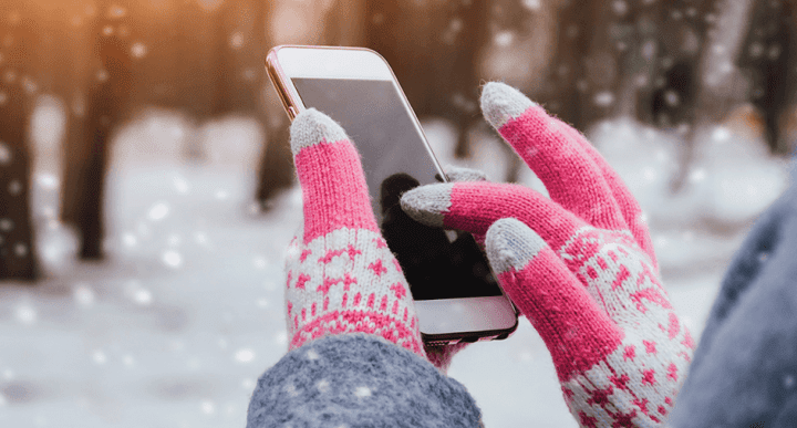 woman using smartphone in the snow
