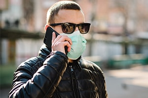 man using phone while wearing mask to protect against COVID-19